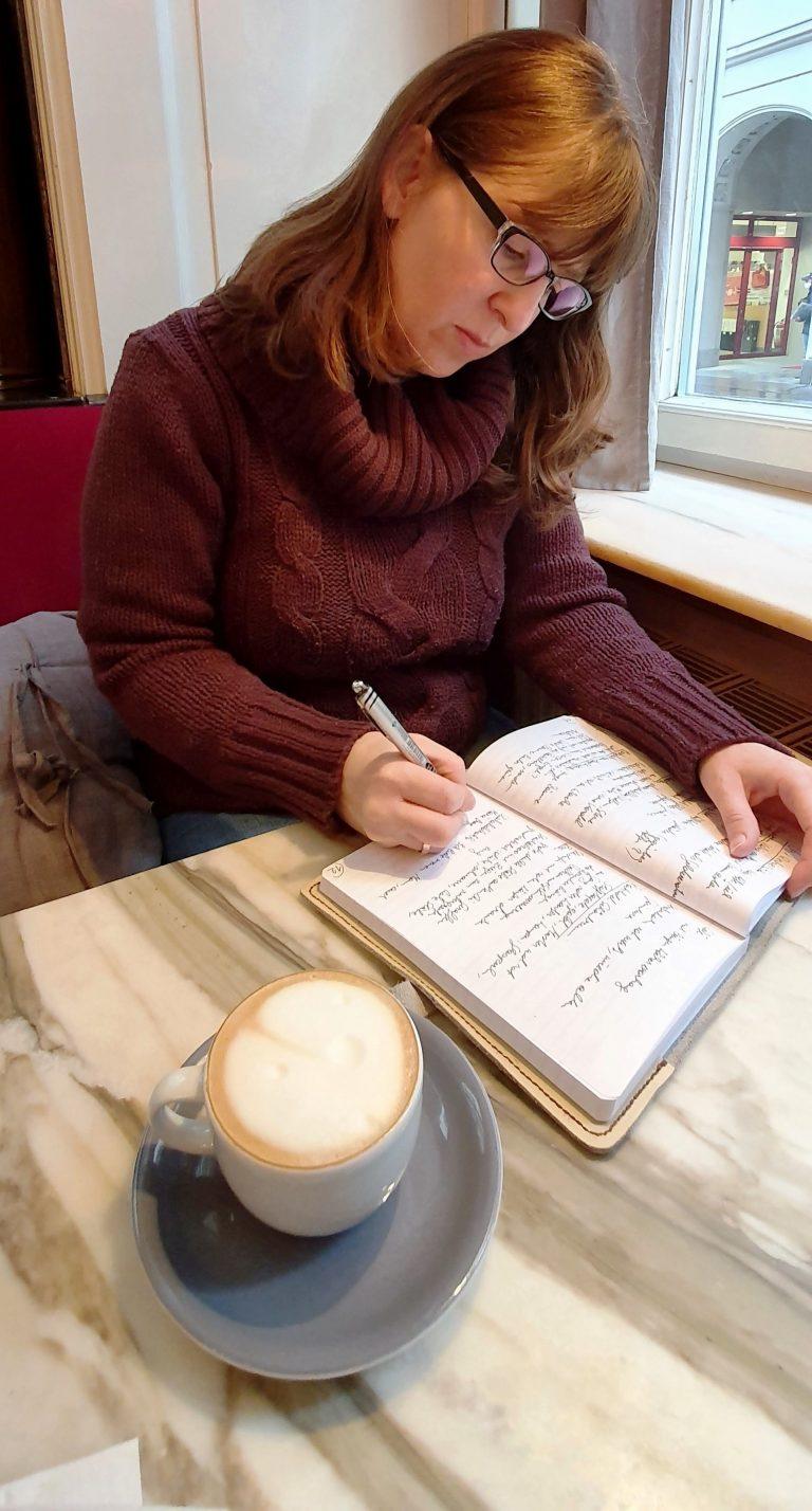 Constanze Scheib in einem Kaffeehaus, schreibt in ein Notizbuch, vor ihr eine Tasse Kaffee