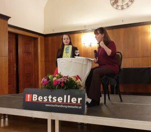 Buchhändlerin Julia Jessenitschnig und Autorin Constanze Scheib an einem Tisch. Constanze Scheib mit einem Mikrofon in der einen Hand, mit der anderen gestikulierend