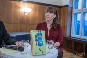 """Autorin Constanze Scheib an einem Tisch sitzend, vor ihr ein Exemplar von """"Der Würger von Hietzing"""""""