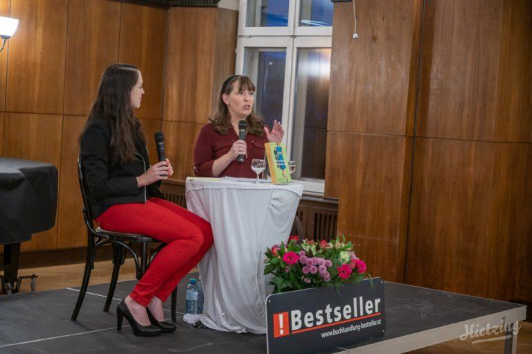 """Buchhändlerin Julia Jessenitschnig und Autorin Constanze Scheib mit Mikrofonen in der Hand auf einer Bühne an einem Tisch sitzend. Auf dem Tisch ein Exemplar von """"Der Würger von Hietzing"""" davor ein Aufsteller: """"Buchhandlung Bestseller"""""""