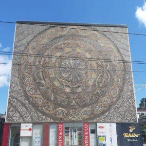 Großes Mosaik an einer Hauswand: Konzentrische Kreise in Brauntönen